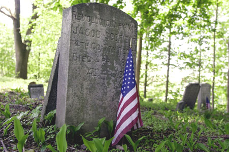 A flag honors the grave of Revolutionary War veteran Jacob Scofield Jr. in a small, historic burial ground known as Simsbury Cemetery at High Ridge Road and Cross Road in Stamford.