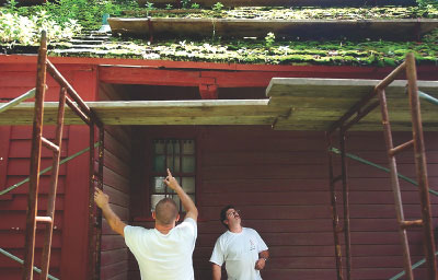 David Hipkins, left, and Stephen Hoyt inspect the roof yesterday of the Hoyt-Barnum House, Stamford's oldest house. Hoyt, a distant relative of the man who built the home, and workers from his firm are installing a new cedar shingle roof