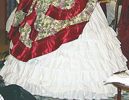 A full skirt fits on top of the  ruffled overpetticoat which covers the hooped crinoline.
