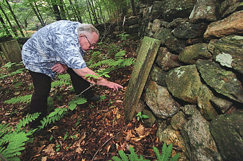 Richard Roberts inspects the headstone on Seth Smith's grave